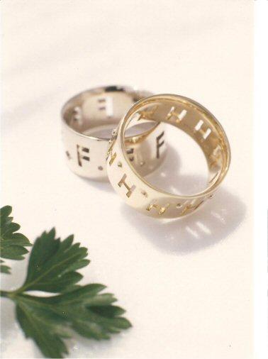 平らな形の指輪にイニシャルHの透かし模様が全周にある18金製の指輪